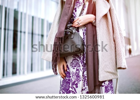 Close up fashion details of young elegant woman posing near modern business center, spring autumn mod season, wearing midi floral dress, cashmere beige coat, taupe scarf and cross body bag. #1325600981
