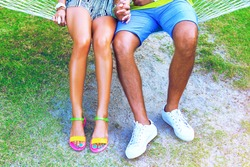 Close up fashion image of couple woman and man legs sitting at the beach, have perfect bronze tan, bearing casual white sneakers and bright neon flat sandals.