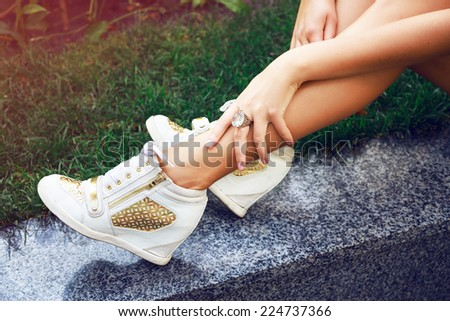 Close up fashion image of woman legs , wearing golden pumped sneakers, and big diamond ring, sitting on the grass, bright colors. #224737366