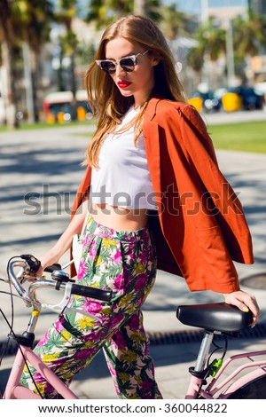 Close up fashion portrait of a young fashionable woman sitting on touring bicycle on Miami street during summer holidays, attractive funky female posing with bike for excursions against palm tree