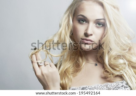 Close-up fashion portrait of Beautiful woman.Flirt Blond Girl with Curly hair.Light.Gray background