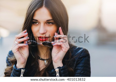 Shutterstock Close up fashion portrait of pretty seductive young woman with sunglasses, posing outdoor. Red lips, wavy hairstyle.