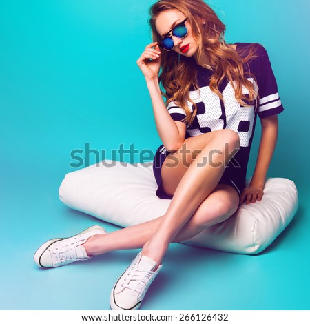 Stock Photo Close up fashion portrait of pretty sportive lady  in stylish sunglasses, basketball t-short and white sneakers sitting on white pillow against bright aqua background .