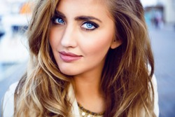 Close up fashion portrait of seductive sexy woman with big blue eyes ,full lips , prefect skin and long fluffy curled hairstyle. Natural make up.