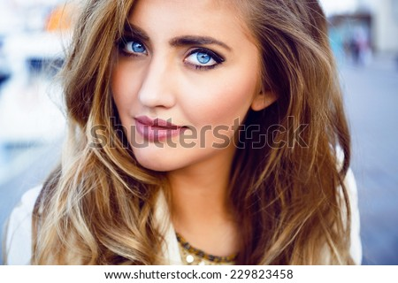 Stock Photo Close up fashion portrait of seductive sexy woman with big blue eyes ,full lips , prefect skin and long fluffy curled hairstyle. Natural make up.