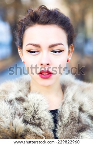 Close up fashion portrait of sensual asian woman with bright make up and perfect skin , wearing fur jacket, posing on the street at autumn fall time. Pastel soft colors.