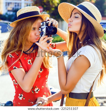 Close up fashion portrait of two funny young pretty blonde and brunette sisters, making funny pictures on retro vintage camera, two stylish best friends having fun together.