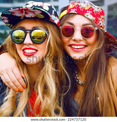 Close up fashion portrait of two sisters hugs and having fun together, wearing bright floral hats and stylish mirrored sunglasses, best fiend enjoy amazing time together.