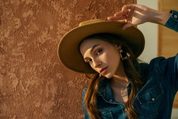 Close up fashion portrait of young confident woman, model, wearing beige wide brim hat, trendy earrings, denim shirt. Copy, empty space for text