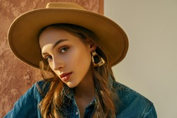 Close up fashion portrait of young confident woman, model, wearing beige wide brim hat, trendy earrings, denim shirt