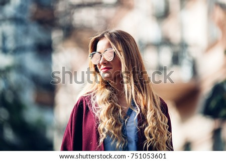 Close up fashion street stile portrait of pretty girl in fall casual outfit Beautiful blond posing outdoor. Girl wearing stylish burgundy coat and red lips - Shutterstock ID 751053601