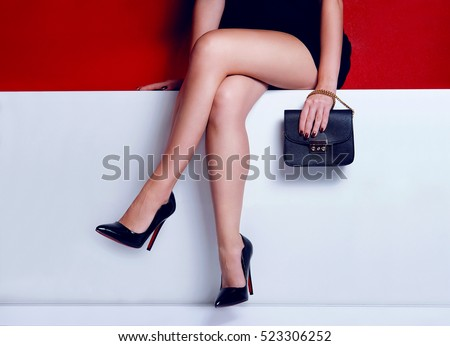 Close up fashion woman legs in short black dress with black handbag and high heels shoes sitting on the white bench.