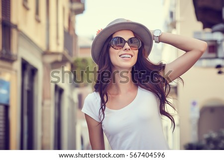 Shutterstock Close-up Fashion woman portrait of young pretty trendy girl posing at the city in Europe,summer street fashion,holding retro fedora hat popular until the 60s.laughing and smiling portrait.