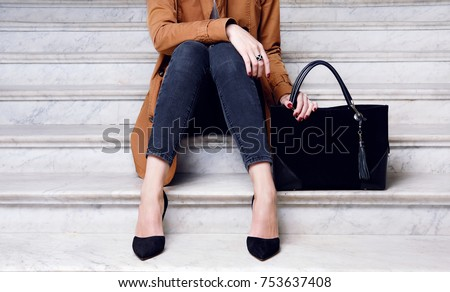 Close up fashion woman sitting in high heel shoes hold black big handbag . Stylish outfit jeans and coat