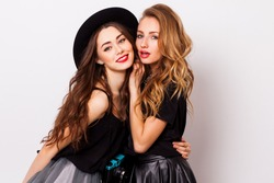 Close up fashionable  portrait  couple of two   cute girls best friends  smiling  and embracing  on white background .Perfect wavy hairstyle. Bright make up. White wall. Black stylish trendy hat.