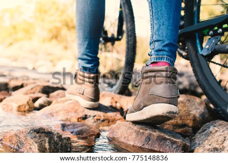 Close up feet hipster women backpack traveling with bicycle on the forest relax time and holiday, color vintage style selective and soft focus