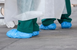 Close up feet of health workers in PPE clothing and blue protective plastic bags on the ground during working in outdoor public area