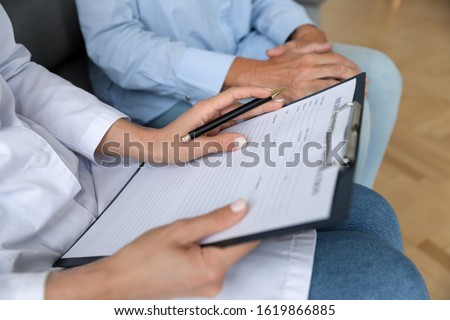 Close up female doctor holding clipboard, filling older patient form, documents, medical history or anamnesis, disease prevention, healthcare, health insurance contract, mature woman checkup