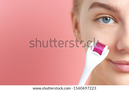 Close-up female face with dermaroller for mesotherapy procedures, skin care at home and in salon. Meso roller with microneedles on pink background