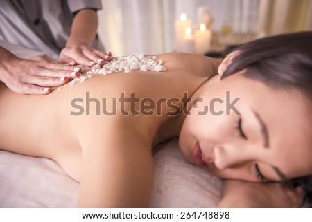 Close-up. Female getting a salt scrub beauty treatment in the health spa.