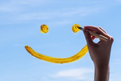 Close-up female hand draws a yellow smile on glass against a blue sky. The concept of joy for a new day, good luck