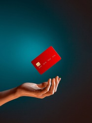 Close up female hand holds levitating template mockup Bank credit card with online service isolated on blue background