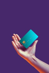 Close up female hand holds levitating template mockup Bank credit card with online service isolated on violet background