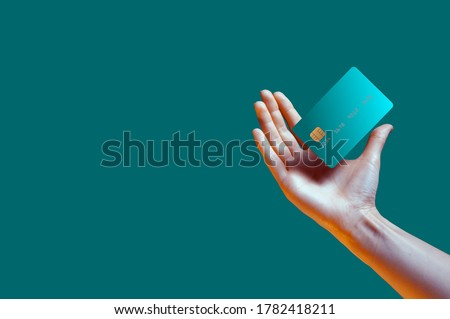 Close up female hand holds levitating template mockup Bank credit card with online service isolated on green background