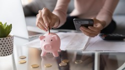 Close up female hands holding smartphone put euro coin into piggy bank, advanced modern tech user using of mobile budget tracking app for personal finances, family money management, e-banking concept