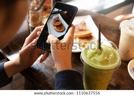 Close up Female hands taking cake, cup of coffee and green tea photos with smart phone.