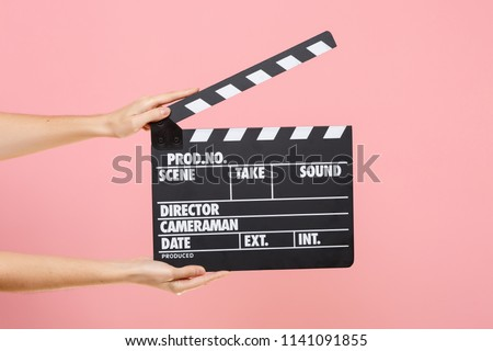 Close up female holding in hand classic director clear empty black film making clapperboard isolated on trending pastel pink background. Cinematography production concept. Copy space for advertising #1141091855