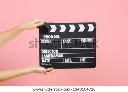 Close up female holding in hand classic director clear empty black film making clapperboard isolated on trending pastel pink background. Cinematography production concept. Copy space for advertising #1148104928