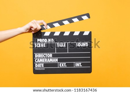 Close up female holding in hand classic director clear empty black film making clapperboard isolated on yellow orange background. Cinematography production concept. Copy space for advertising #1183167436