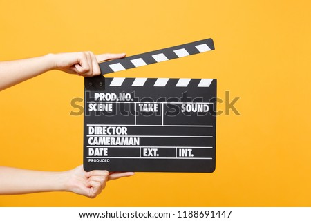 Close up female holding in hand classic director clear empty black film making clapperboard isolated on yellow orange background. Cinematography production concept. Copy space for advertising mock up