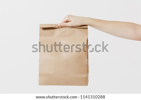 Close up female holds in hand brown clear empty blank craft paper bag for takeaway isolated on white background. Packaging template mock up. Delivery service concept. Copy space. Advertising area #1141310288