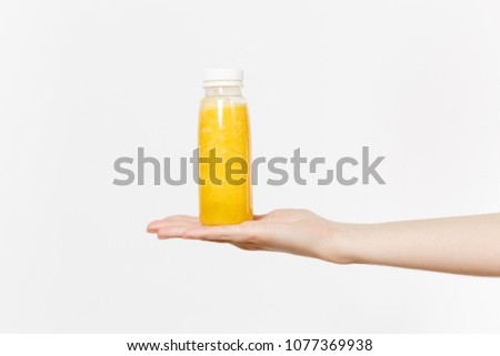 Close up female holds in hand on palm yellow detox smoothies in bottle isolated on white background. Proper nutrition, vegetarian drink, healthy lifestyle dieting concept. Advertising area copy space
