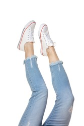 Close-up female legs in blue jeans and sneakers isolated on white background