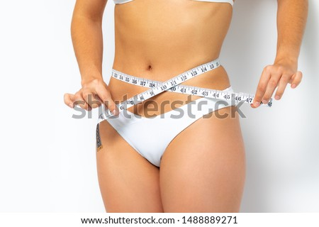 Close up female waist in white bikini. Hands measuring waist with metric band.