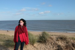 Close up female wearing mask in beach landscape, dark haired woman in red  jacket scarf hat standing on grass sand dunes by ocean in Covid-19 virus lockdown for  outbreak with Winter blue skies