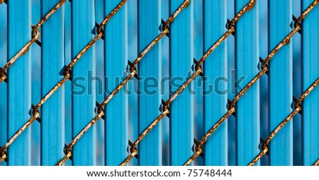Close-up Fence Detail of Chain Link Showing Rust with Solid Blue Infill Slats