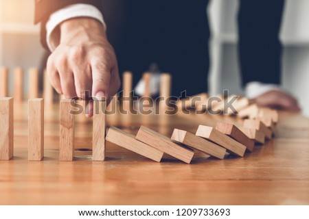 Close up finger businessman stopping wooden block from falling in the line of domino with risk concept. #1209733693