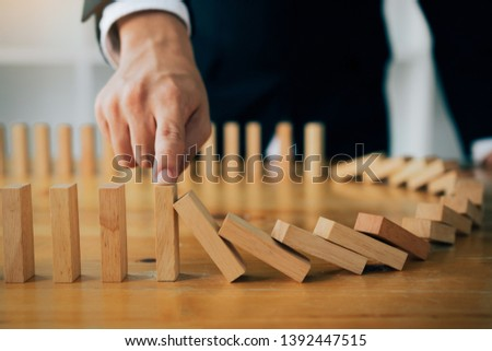 Close up finger businessman stopping wooden block from falling in the line of domino with risk concept. #1392447515