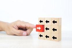 Close-up finger pushing cube wooden toy block stacked with arrow icon pointing to opposite directions for way of adapting to change leader and transform concept.
