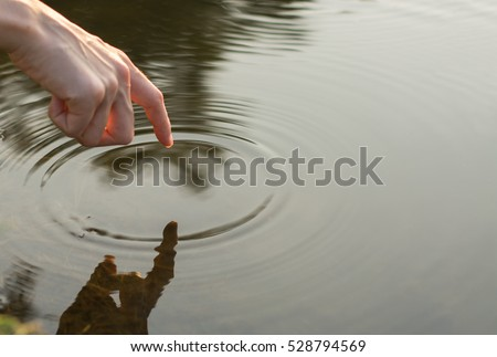 Close up finger touches water and drop of water falling and creating natural and calm waves,calmly concept,