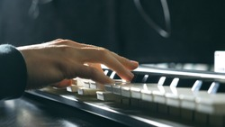 Close up fingers of pianist at the piano keys. Mens arms plays solo of music or new melody. Hands of male musician playing at synthesizer. Slow motion Top view Isolated shot.