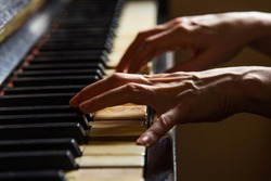 Close up fingers of woman pianist at the rusty piano keys, arms plays solo of music. Hands of female musician playing. Music instrument, solo pianist, song composer, hobby, practice stu