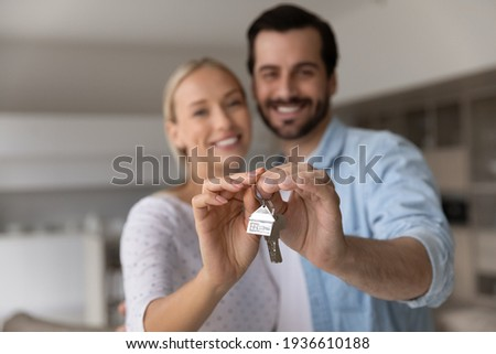 Close up focus of happy young Caucasian couple show keys to first share own apartment or house. Smiling millennial man and woman celebrate relocation to new home. Moving, rental, estate concept. Foto stock ©