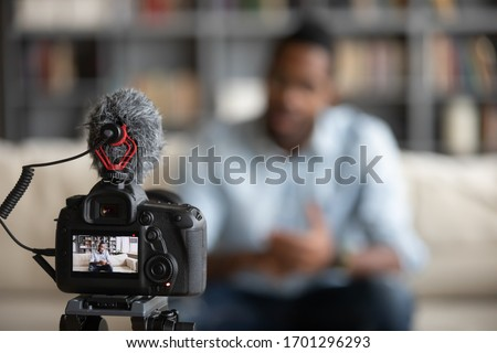 Close up focus of modern professional camera shooting african American male coach or tutor making vlog, biracial man blogger talk with subscribers record video tutorial on web cam, technology concept