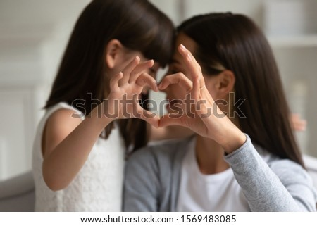 Close up focus of mum and kid girl fingers showing heart symbol, mother with little daughter touching with noses enjoy sweet moment of love tenderness. Children are life value, meaning of life concept