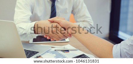 close up focus on businessman hand shake with businesswoman after completed deal of company profit in office meeting room concept